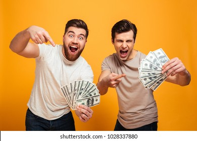 Portrait of a two excited young men holding bunch of money banknotes and pointing fingers isolated over yellow background