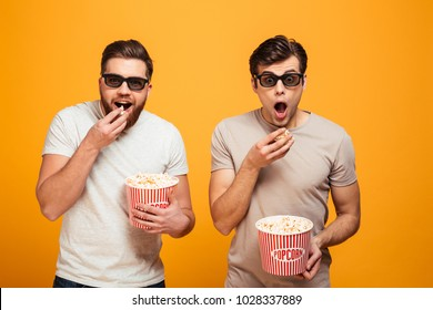 Portrait of a two excited young men in 3d glasses watching movie and eating popcorn isolated over yellow background