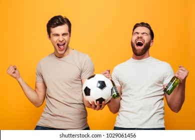 Portrait of a two excited young men holding beer bottles and soccer ball isolated over yellow background