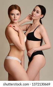 Portrait of two fashionable attractive women in  lingerie looking at each other and posing
