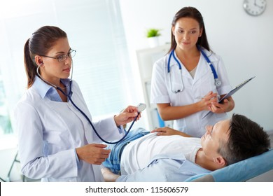 Portrait of two female doctors looking at patient during medical treatment in hospital
