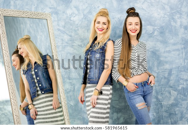 Portrait of two female friends dressed casualy near the mirror on the blue wall background