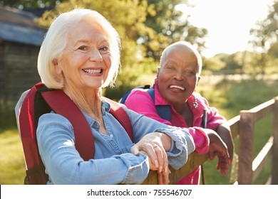 Portrait Of Two Female Senior Friends Hiking In Countryside