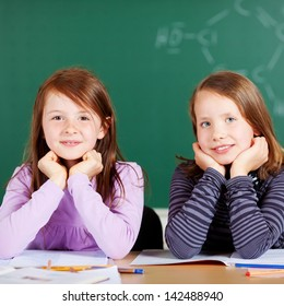 Portrait of two female students smiling and sitting inside the classroom