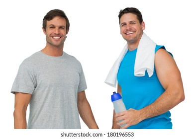 Portrait of two fit young men with water bottle and towel standing over white background