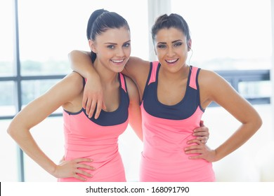 Portrait of two fit young women smiling in a bright exercise room