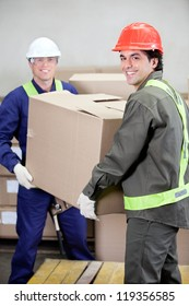 Portrait of two foremen lifting cardboard box in warehouse