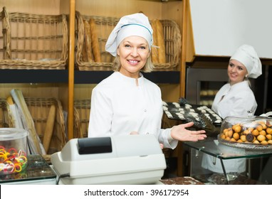 Portrait of two friendly female bakers with pastry in bakery