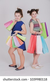 Portrait of two friends with shopping bags in hands over white background