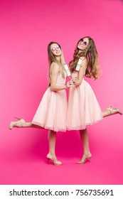 Portrait of two funny and sweet girls, in pink dresses, sunglasses like princes or candies, having fun and sending kiss at camera. Pretty women dancing, jumping, smiling. Fashion, shopping, sale.