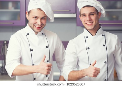 Portrait of two funny working men in cook uniform showing OK sign (thumbs up) and posing in modern kitchen together. Close up. Indoor shot
