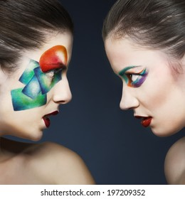 portrait of two girls with a colored make-up in studio