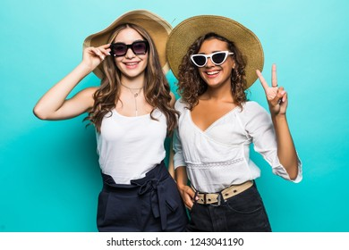 Portrait of two girls with different type of skin wearing straw hats and summer clothing isolated over blue background
