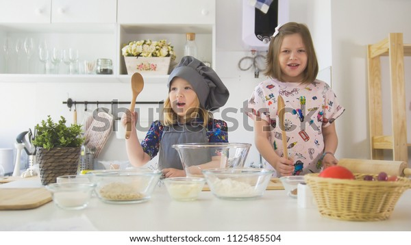 Portrait of two girls on the kitchen before cooking
