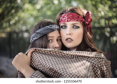 Portrait of two girls outdoors. The concept of difficult teenagers. Representatives of youth subcultures. Vintage and retro.