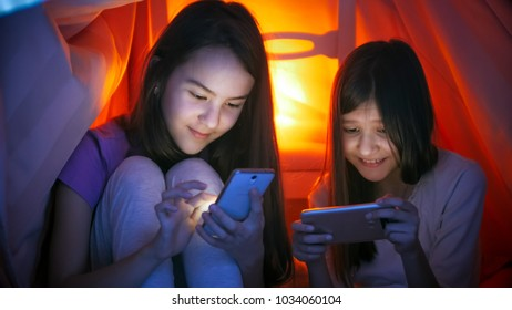 Portrait of two girls in pajamas with mobile phones at night - Shutterstock ID 1034060104