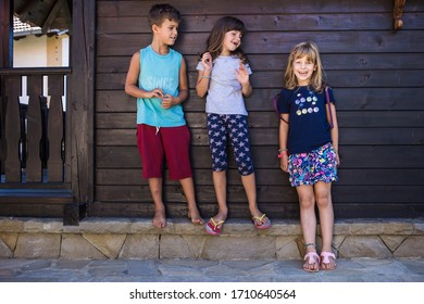 Portrait of two girls, sisters and their boy friend, enjoying summer, smiling and making funny faces. International Childrens Day concept