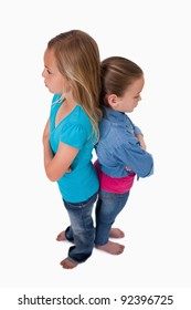 Portrait of two girls standing back to back against a white background