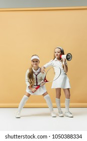 Portrait of two girls tennis players holding tennis racket. Studio shot. Pastel background. Stylish young teen girls posing at studio. Sport style. Teen and kids fashion concept. children's fasion