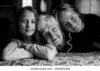 Portrait of two girls and their grandmother. Black and white photo.
