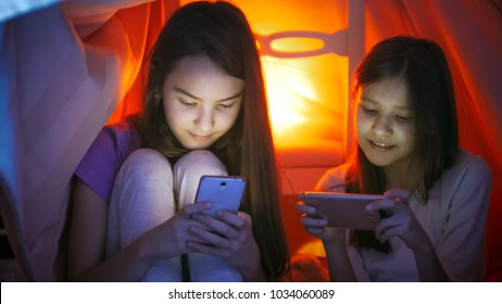 Portrait of two girls typing message in social media on mobile phones in bedroom at night - Shutterstock ID 1034060089