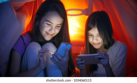 Portrait of two girls typing messages on mobile pnones at night - Shutterstock ID 1034060113