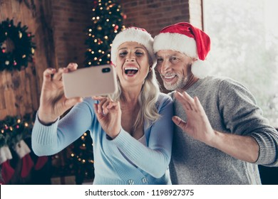Portrait of two glad excited ecstatic nice charming adorable stylish trendy grey-haired married spouses grandma granddad showing taking making selfie on device gadget waving hi hello