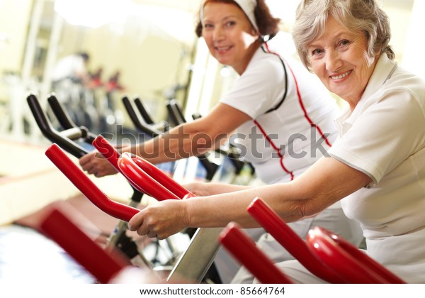 Portrait of two good-looking senior women training on exercise machines