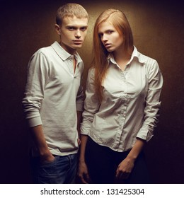 Portrait of two gorgeous red-haired (ginger) fashion twins in white shirts posing over golden background together. Studio shot.