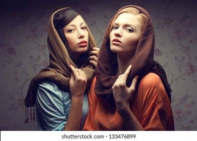 Portrait of two gorgeous young women (brunette and red-haired) in shawls and vintage dresses. Retro (classic, hollywood) style. Perfect hair, skin and make-up. Studio shot