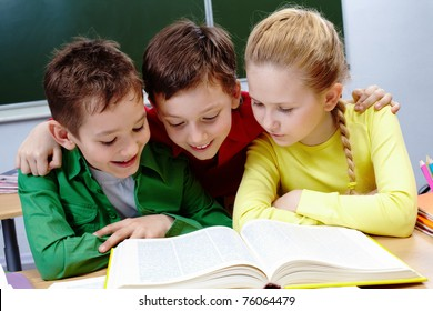 Portrait of two guys and girl reading book in classroom