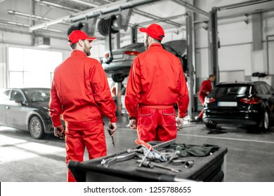 Portrait of a two handsome auto mechanics in red uniform standing together at the car service
