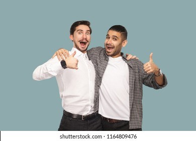 Portrait of two handsome bearded happy friends or partners standing hugging, and looking at camera with satisfied amazed face and thumbs up. indoor studio shot, isolated on light blue background.