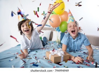 Portrait of two happy adolescent boys on sofa in birthday cone caps, kids are delighted with confetti flying around. Colorful balloons on background