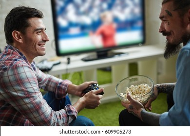Portrait of two happy adult men with tattoos enjoying video game competition and  smiling cheerfully holding wireless controller while sitting on couch in living room, talking and eating popcorn