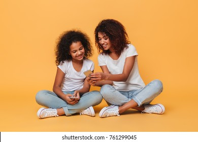 Portrait of a two happy afro american sisters using mobile phones while sitting isolated over orange background