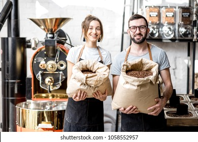 Portrait of a two happy baristas in uniform standing with bags full of coffee beans at the coffee store