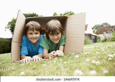 Portrait of two happy boys lying in cardboard box in the backyard