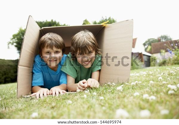 Portrait of two happy boys lying in cardboard box in the backyard