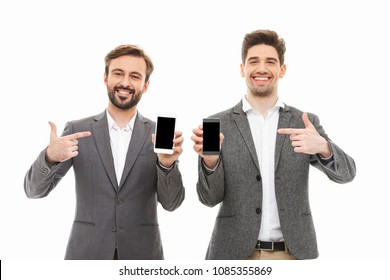 Portrait of a two happy business men showing blank screen mobile phones and pointing fingers isolated over white background
