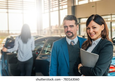 Portrait of two happy car sales consultants working inside vehicle showroom.