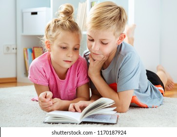 Portrait of two happy children reading a book on the floor at home