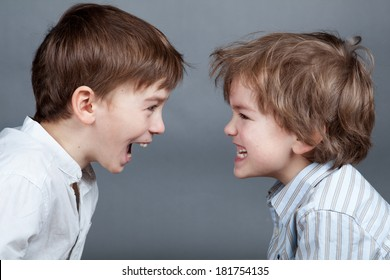 Portrait of two happy cute brothers on gray background, indoors, studio