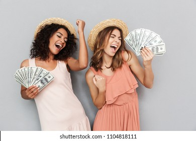 Portrait of two happy delighted girls with different type of skin wearing straw hats rejoicing win and dancing while holding fans of cash money isolated over gray background