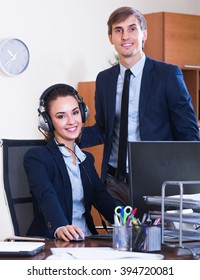 Portrait of two happy help line consultants at workplace
