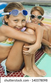 Portrait of two happy little girls sitting on the edge of a swimming pool