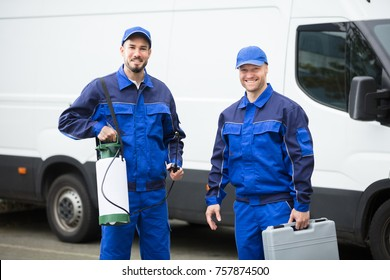 Portrait Of Two Happy Male Pest Control Workers With Toolbox
