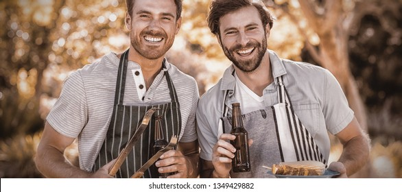 Portrait of two happy men holding barbecue meal and beer bottle in park