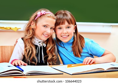 Portrait of two happy schoolgirls in a classroom.