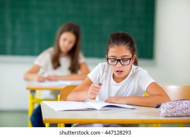 Portrait of two happy schoolgirls in a classroom, selective focus